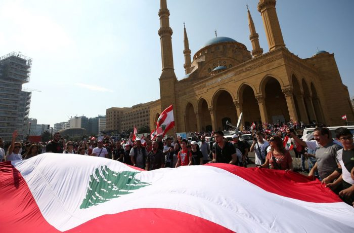 Manifestantes carregam bandeiras nacionais durante um protesto contra o governo no centro de Beirute, Líbano, em 20 de outubro de 2019 (Foto: ALI HASHISHO)